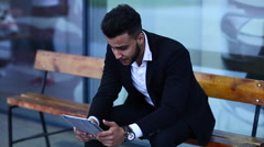Man in suit arabic use tablet  bored tired near business center Stock Footage