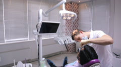 Man dentist makes a first examination of patient lying in chair in dental office Stock Footage