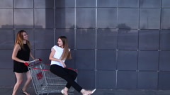 Girl runs, rolls friend in the shopping cart Stock Footage