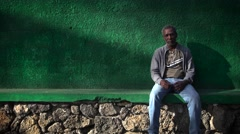 Portrait of Mauritian man  sitting aginst colourful wall Stock Footage