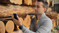 Young man forestry engineer touch phone in front of wood Stock Footage
