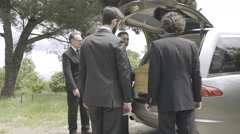 Pallbearers in Hearse arriving with coffin at graveyard - stock footage