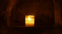 Candle in abbey at St Guilhem le Desert, Cevennes France Stock Footage