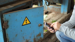 Male hand is holding a modern touch screen phone and blur image of old factory Stock Footage
