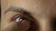 Young man removes contact lens Stock Footage
