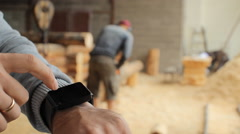 Young man forestry engineer touch smart watch in front of wood Stock Footage