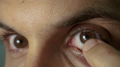 Young man put in contact lenses Stock Footage