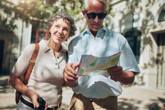 Mature man and woman using  map while sightseeing. Stock Photos
