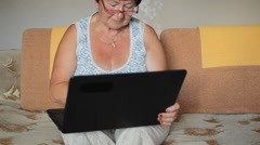 Woman wearing glasses sitting on a sofa at home concentrating as she works on a - stock footage