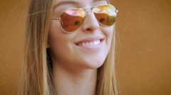 A beutiful blond young women smiles and takes off her sunglasses - stock footage