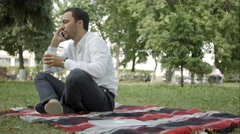 Call me anytime. Cheerful young man talking on the phone sitting on the grass in Stock Footage