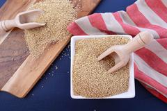 White grain quinoa on blue wood background. Stock Photos