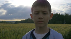 Boy walks through a field of corn, face close up, slow motion Stock Footage