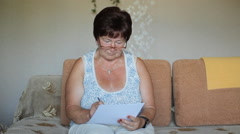 Senior woman signing a contract at home. She carefully reads and signs the Stock Footage