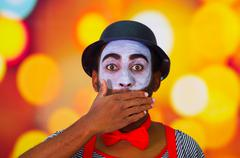Headshot pantomime man with facial paint posing for camera using hands to cover Stock Photos