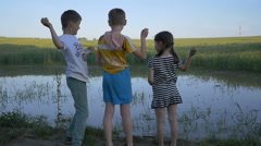 Children throwing stones in the water in the field, slow motion - stock footage