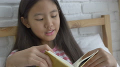 4K : Asian preteen girl reading story book on the bed Stock Footage