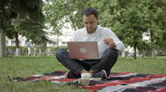 Freelancer man with laptop at summer park on bright day. Man in casual working Stock Footage