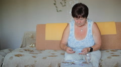Elderly sick woman chooses the desired tablet at home. It takes one and drinks Stock Footage