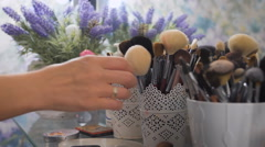 Makeup brushes, next to blue flowers, closeup Stock Footage