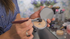A makeup artist using a brush with the powder Stock Footage