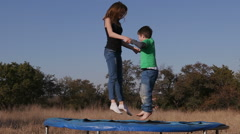 Slow motion of teenager girl and young boy having fun jumping on a trampoline Stock Footage