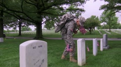 Arlington National Cemetery - Soldier places flag at grave then salutes Stock Footage