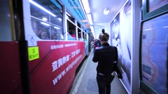 Passengers going in and out from the modern Hong Kong two-storeyed tramway Stock Footage