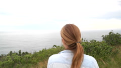 Slow Motion of Female Sitting on Bench Overlooking Beautiful Ocean View Stock Footage
