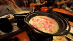 Adding meat to the boiling chinese traditional meal. Stock Footage