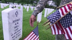 Arlington National Cemetery - soldier placing flags at graves Stock Footage
