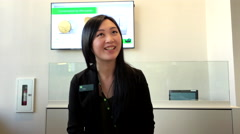 Attractive asian clerk helping customer to deposit cheque inside TD bank Stock Footage