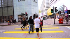 People cross the road using pedestrian crosswalks. Passing by luxury Dior store. Stock Footage