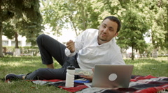 Attractive man at lunch time in the park, say something on the camera Stock Footage