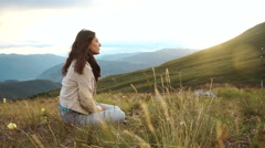 Young woman enjoying beautiful sunset sitting on the mountain with great view on Stock Footage