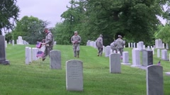 Arlington National Cemetery - soldiers place flags at grave sites Stock Footage