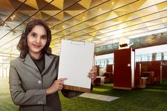 Customer service operator woman with headset smiling show empty paperboard Stock Photos