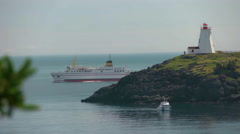 Large Ferry Boat Drives Past Lighthouse with Small Boat in Foreground. Stock Footage