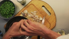 Male hands mixing chopped garlic, greens, pepper and butter Stock Footage