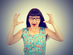 Young woman in glasses screaming in horror, grimace Stock Photos