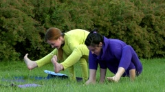 Yoga in the Park. Two Girls Trying to Balance on the Hands. They Fall Down and Stock Footage