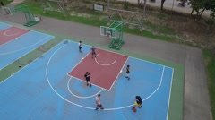 Aerial of man running to save the basketball going out of bounds Stock Footage