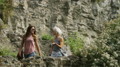 Two attractive young women walking a rocky beach path and talking Stock Footage