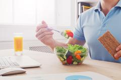 Unrecognizable man has healthy business lunch in modern office interior Stock Photos