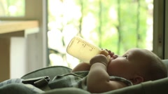 Baby eating milk from bottle Stock Footage