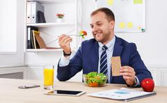 Man has healthy business lunch in modern office interior - stock photo
