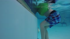 Underwater shot of a little boy climbing out at the pool Stock Footage