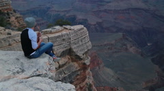 Young man playing ukulele at the edge of a cliff at Grand Canyon Stock Footage
