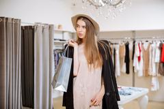 Woman standing and holding shopping bags in fashion boutique Kuvituskuvat