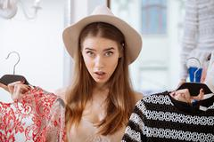 Puzzled young woman choosing clothes in clothing store Stock Photos